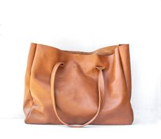 """Classic raw edged leather shopper. This classic shopper bag is large in size and perfect for your every day. Its simple raw edged and unlined. Made from ... all over the world for its fine leather purses handbags totes and accessories.The Dooney & Bourke Large Leather Tote Handbag is all you will need f...se times when you need extra room in your handbag for travel carrying """"kid things"""" or simply to be able to put all of your items in one bag for easie #Helen.stephenharrisfashions.com… Black Patent Leather, Red Leather, Leather Bag, Brown Leather Totes, Tote Handbags, Tote Purse, Tote Bags, Shopper Bag, Bucket Bag"""