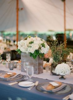 Pretty tablescape with light charcoal gray linen tablecloth, linen runner, tall distressed wood vase with white flowers, mix of pretty votives, tall wildflower looking plant in a mercury glass vase with moss