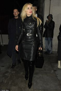 Blonde in black leather strappy buckled harness leather dress and black patent leather thigh boots