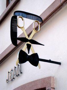 Rotulos de una peluqueria, donde los peines hacen efecto del pelo, las tijeras hace forma de los ojos y de la cara, con una pajarita y un bigote elegantes, dando a entender que es una peluqueria para gente con dinero.  muy original y llamativo. Alejandro Estevez