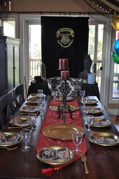 Harry potter table decorations - LOVE the Hogwarts Crest and the black tulle with lights above the table. screw kids, this party is for me! Mesa Do Harry Potter, Harry Potter Adult Party, Harry Potter Table, Harry Potter Fiesta, Estilo Harry Potter, Harry Potter Halloween Party, Harry Potter Baby Shower, Harry Potter Wedding, Harry Potter Christmas
