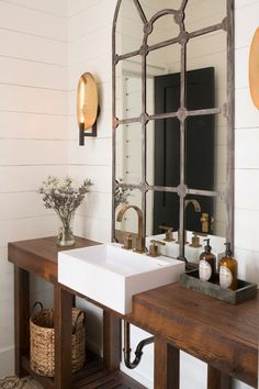 The metal framed mirror, white farmer's sink vanity and refinished wood counters mix together to create a beautiful, rustic powder room.