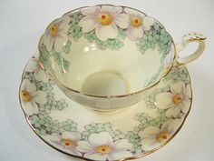 Gorgious tea cup and saucer from Paragon, England. Model: April Light yellow tea cup set with hand painted flowers and leaves. The backstamp date this cup & saucer from 1939 - 1949 Gold trimmed. Cup Measures: 2 1/8 high & Saucer Measures 5 5/8 diameter Very good conditon, no
