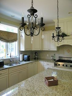 @Dana Armstrong Hee Aldridge  Your idea for your  kitchen is similiar to this! Double iron and crystal chandeliers and creamy ivory cabinets