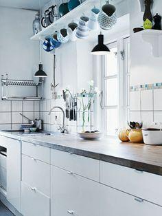 white kitchen with black pendant lights, under shelf hooks