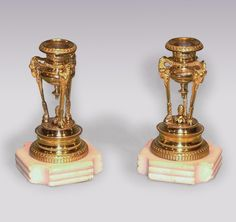 A fine quality pair of early 19th Century Regency period ormolu Candlesticks, having leaf and berry nozzles above triple ramshead supports, raised on engine turned beaded socles, ending on reeded white marble bases. Circa: 1810 Ref: 5687