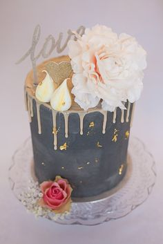 Artisana - Bespoke Cakes  Tall drippy grey cake with pale pink chocolate ganache drip, topped with roses and meringue kisses and gold leaf