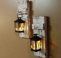 This Rustic candle holder, hanging lantern sconce is made from reclaimed pallet wood. The little lanterns are approx. 3 x 3 x 4. The wood has natural holes, cracks to give it that rustic look. These are distressed white. There are various stain options available. Item may not be exact one pictured but will be unique and similar in look and style. It comes with a battery operated tea candle and a small black lantern. It measures approx. 10 x 5  Please Note the Price is for 1 wood sconce with…