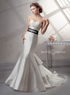 Dramatic fit and flare wedding dress, Vivien by Sottero and Midgley, featuring a modern tiered train and soft, scoop neckline. Available with detachable grosgrain ribbon belt.