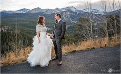 Bride and groom hold hands for a portrait in front of the pretty Breckenridge mountains with the ski slopes during fall in Colorado. - April O'Hare Photography http://www.apriloharephotography.com