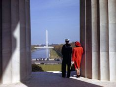 A man and woman look out at the Reflecting Pool and Washington Monument from the Lincoln Memorial.