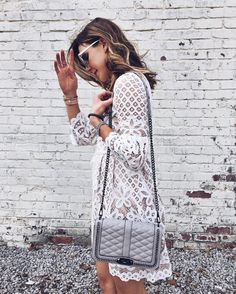 Intricate white lace featuring a grey cross-body bag.