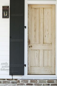 bleached door w/black shutters, stone foundation