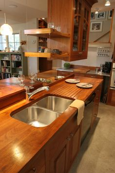 Custom solid wood face grain Teak counter top with integrated sloping drain board and under mount sink.