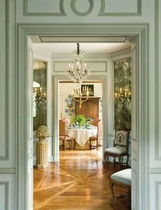 Elegant interior with beautiful trim work; occasional chairs add a welcoming dimension to the entry