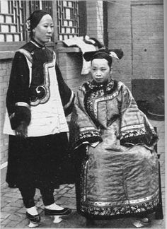 Chinese women - Two Manchu women in a courtyard - Manchu women did not bind their feet, but wore elevated shoes that created some of the visual effects of bound feet.