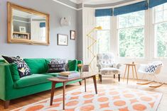 The Pink House living room with Jennifer Manners ikat circles rug, IKEA Stockholm green velvet sofa, yellow Jielde floor lamp