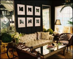 Dark paint on paneling, seagrass wall-to-wall carpeting, zebra hide accent chairs, cream tufted sofa