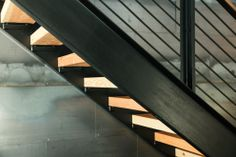 A straight staircase with wooden steps and a black metal railing, perfect for modern and contemporary houses. - Oneflare