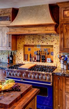Rustic wood kitchen cabinets with beautiful wood grain are paired with dark brown countertops and earth-toned tiled backsplash in this Mediterranean kitchen A pro-quality bright blue oven adds a burst of color to the space Dark Wood Kitchens, Rustic Kitchen Cabinets, Kitchen Countertops, Cool Kitchens, Kitchen Wood, Brown Cabinets, Wood Cabinets, Kitchen Backsplash, Kitchen Hutch