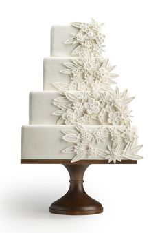 Cake by Charm City Cakes Four tiered traditional wedding cake. White with cascading white flowers. Stand by Sarah's Stands
