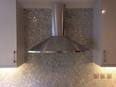 Close up of marble mosaic kitchen back splash at cooker hood.
