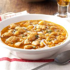 """Spicy Chicken and Hominy Soup Recipe -This slow-cooked soup is also called """"posole,"""" a traditional good luck New Year's meal in my native New Mexico. Everyone makes it differently—my soup answers the age-old chili question, """"Red or green?"""" by using both!—Janet Christine McDaniel, Arlington, Texas"""