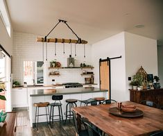 Clean-lined furniture and industrial surfaces are given rustic warmth to this family home in Waihi Beach with wooden slabs and bountiful botanicals. Home Building Tips, Building A House, Barn Style Doors, Barn Doors, Inside Home, Kitchen Stools, Minimalist Kitchen, Dining Room Design, Home Renovation