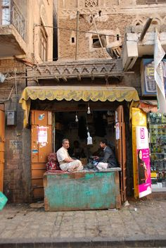 like the awning over the stall and the color of the washed out wall that they are sitting on  sana'a, yemen