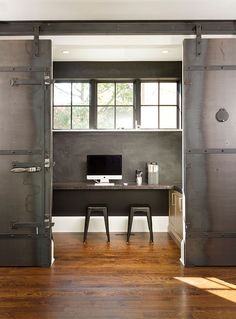 Dramatic sliding doors separate the small home office from kitchen and dining area