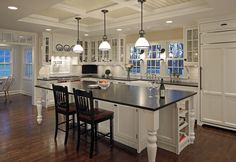"""Farmhouse style kitchen; with glass door display cabinets, coffered ceiling, pendants over large island with decorative  support """"posts"""""""