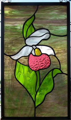 Woodsy piece with colorful background glass and bright pink and white lady slipper flower. Tall panel best hung in window comes with chain and hook to hang.  Measures 10.5 x 18.625 inches