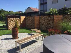 Wohnraum Garten. LIGUNA Holzlager aus Cortenstahl in Kombination mit Lärche Rombus Sichtschutz..