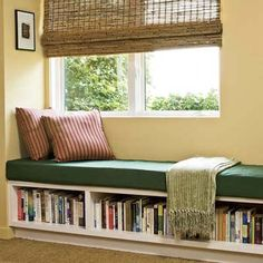 Bookshelves with bench under the window window blinds strip patterns decorative pillows book arrangements