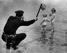 From the waters edge a New York policeman urges two young children to put their bathing costumes back on. (Photo by Ed Clarity/Keystone/Getty Images). July 1949