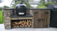 Primo Grill with storage for wood and reclaimed wood door front.
