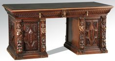 Italian Renaissance Revival double pedestal desk, 19th century, executed in walnut, the top, with inset leather writing surface and conforming piece of protective glass, carved with gadrooned borders and lion's head masks with brass rings, surmounting paneled doors with geometric designs carved in relief with egg and dart borders, flanked by cherubic term figures ending in foliate garlands