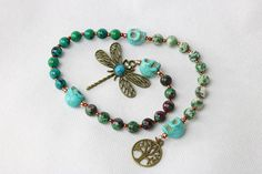 Ruby in fuchsite,chrysocolla, green moss agate & turquoise howlite gemstone crystal beads lend there metaphysical energies to this beautiful set of pagan prayer beads. A dragonfly pendant is featured on the end of these prayer beads & a Tree of Life charm adorns the other end. This is