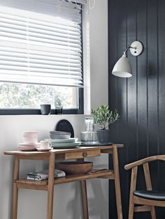Stylish wall light idea for your dining room: The advantage of wall lights is that you can direct the light. This classic shaped design has a bone china shade that can be swivelled making it a great choice for dining areas. Choose a contrasting colour for impact - this putty grey colourway looks striking against the dark grey of this panelled wall. Visit housebeautiful.co.uk for more inspiration.