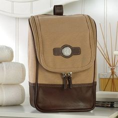 A luxury gift built for men who travel, this roomy 7 x 11 tan canvas and brown leather kit bag personalized with a three letter monogram will keep your groomsmen's toiletry items organized