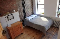 Minimalist bedroom with wood floors and brick wall | no trash project