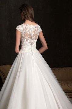 Allure Bridals 9058 is a beautiful, A-line gown with a simple, full skirt that falls floor length with a traditional train in the back. The bodice features elegant lace detailing with a gorgeous, sheer lace neckline, complimenting the sheer lace, open-back with buttons lining the zipper.
