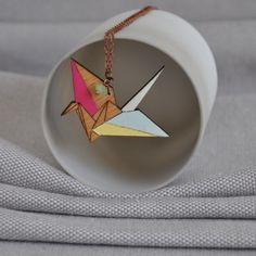 The origami style necklace from ArtySmartyShop.com is made from birch wood, carefully hand painted in lovely bright pink, yellow, pale blue and cream pastel colours and finished with a durable varnish. The chain is an vintage style antiqued copper with a lobster clasp, glass bead and 'artysmarty' rabbit tag. There are also matching brooches in this series.  #woodcarving #lady #crafting #jewelrydesign #fashion #accessory