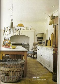 Love this rustic kitchen with the oven recessed + antique table/island