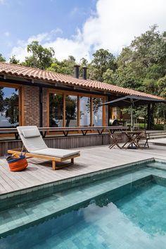 Decoração de casa de campo com madeira. Na varanda plantas, piscina e bancos de madeira, mesa de madeira, cadeira de madeira, janelas de madeira.