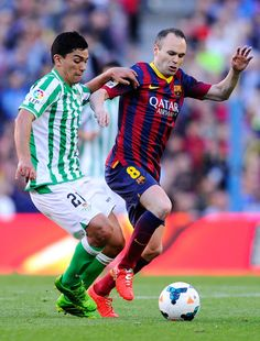 Andres Iniesta of FC Barcelona duels for the ball with Lorenzo Reyes of Real Betis Balompie during the La Liga match between FC Barcelona and Real Betis Balompie at Camp Nou on April 5, 2014 in Barcelona, Catalonia.