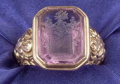 14kt Gold and Amethyst Intaglio Ring, with carved escutcheon, high relief floral and foliate shoulders,