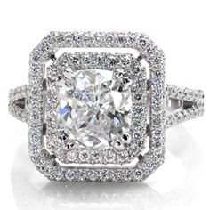 This stunning ring is covered in micro pave and will sparkle from all angles. The cushion cut center diamond is surrounded by two separate halos. The band is a split shank and underneath the halos, on the side view of the band, there is hand made filigree detailing. Design 2369 from Knox Jewelers