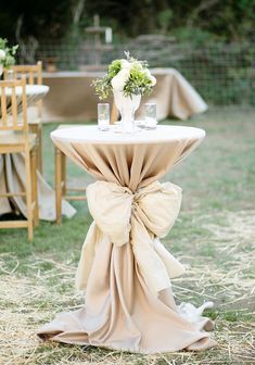 Pretty cocktail table cinched with a bow. Something like this with, maybe different heights with large floral arrangements? Just beautiful!