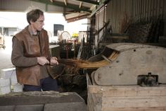 Credit: Sam Frost Coate demonstrates an older machine for stripping willow rods, dating back to the 1920s and in daily use until 2002. The w...